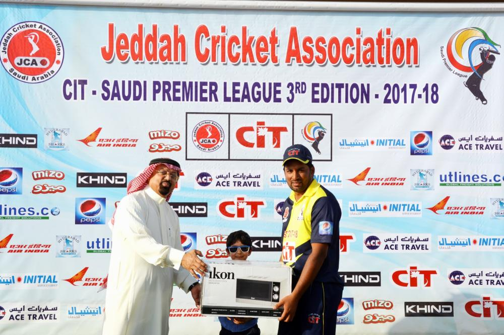 Amir Wahla receiving the Man of the Match award from Dr Faiz Abideen.