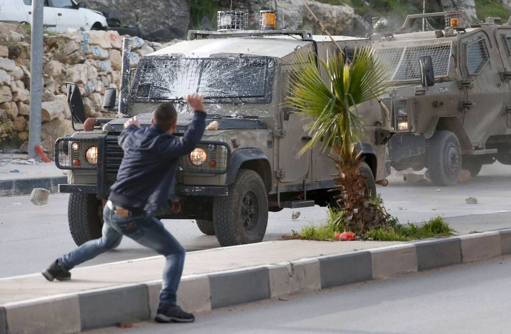 Palestinians throw stones at Israeli army vehicles after forces entered the village of Halhoul in the occupied West Bank, Wednesday. A Palestinian stabbed a security guard at the entrance to an Israeli settlement and was shot dead in the latest violence in the occupied West Bank, Israel's military said. — AFP