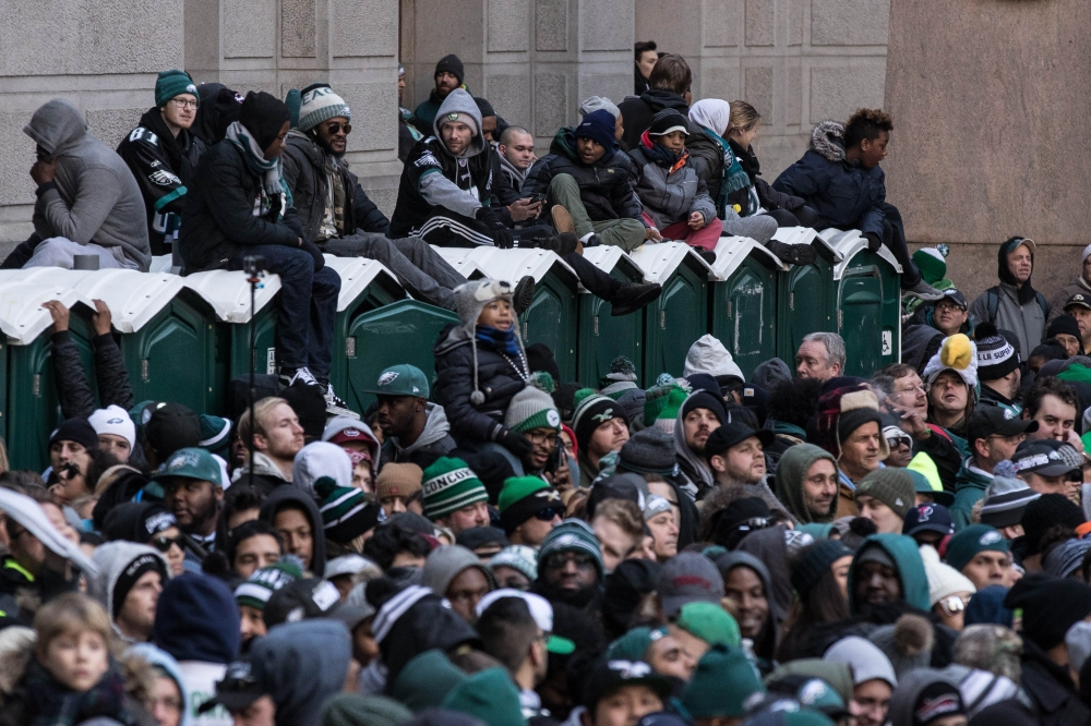 Philadelphia Eagles fans sit on top of portable toilets to gain a better view of the Super Bowl LII Championship parade at City Hall. — Reuters