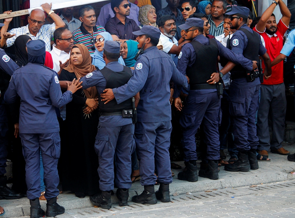 Maldivian Police officers push back the opposition supporters near the main opposition Maldives Democratic Party (MDP) headquarters during a protest demanding the government to release jailed opposition leaders, including former Presidents Mohamed Nasheed and Maumoon Abdul Gayoom in line with a last week Supreme Court order, in Male, Maldives on Friday. — Reuters