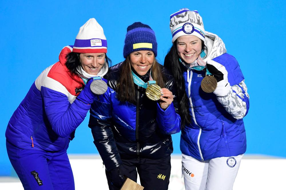 Sweden's Charlotte Kalla (C), Norway's Marit Bjoergen (L) and Finland's Krista Parmakoski celebrate on the podium during the medal ceremony at the end of the women's cross-country skiathlon event at the Pyeongchang 2018 Winter Olympic Games Saturday. — AFP