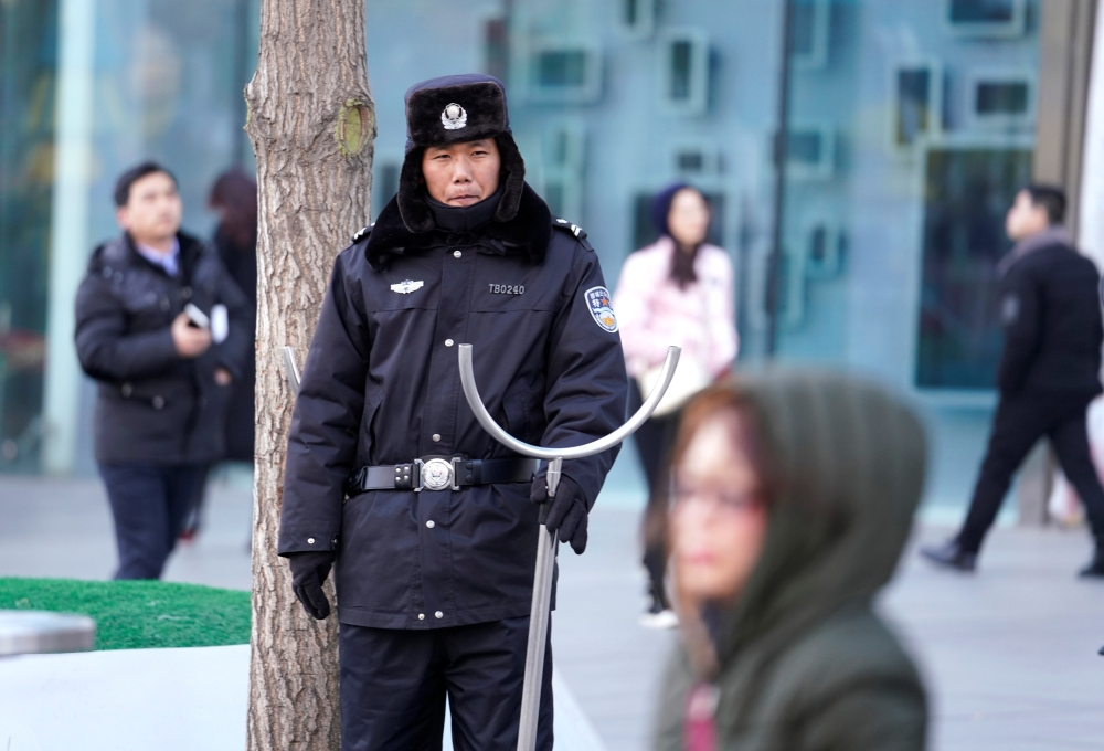 Security personnel stand guard outside the Joy City Mall in the Xidan district after a knife attack, in Beijing, China, on Sunday. — Reuters