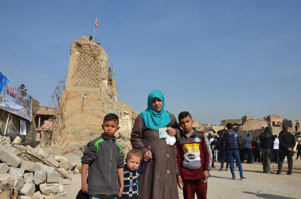 Iraqis stand in front of the destroyed Al-Hadba minaret at the Al-Nuri Mosque in Mosul's Old City during a gathering to call on international organizations to proceed with the reconstruction of the city. — AFP