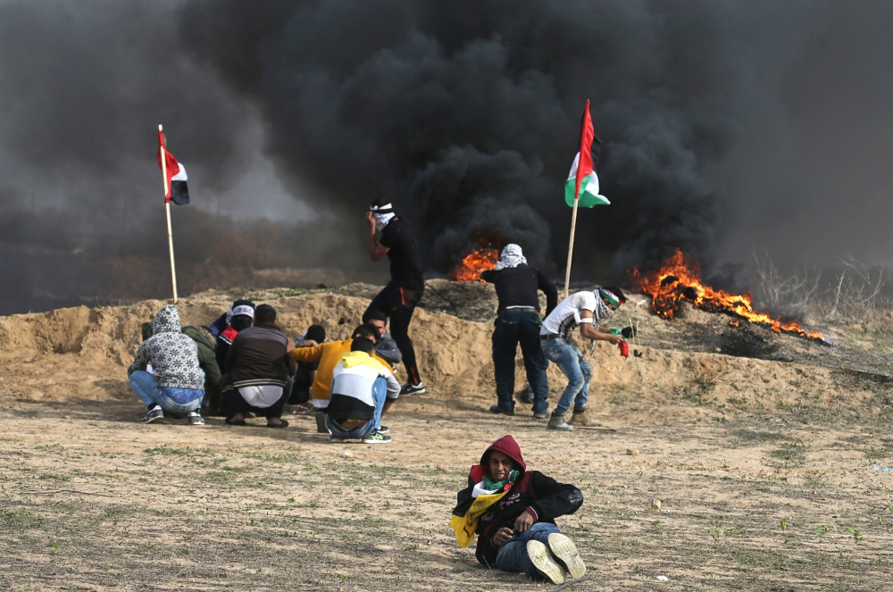 Palestinian demonstrators take cover during clashes with Israeli troops, near the border with Israel in the southern Gaza Strip. — Reuters