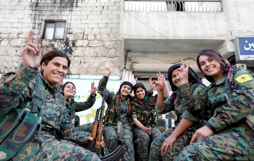 Kurdish female fighters of the Women's Protection Unit (YPJ) gesture in the Sheikh Maksoud neighborhood of Aleppo. — Reuters