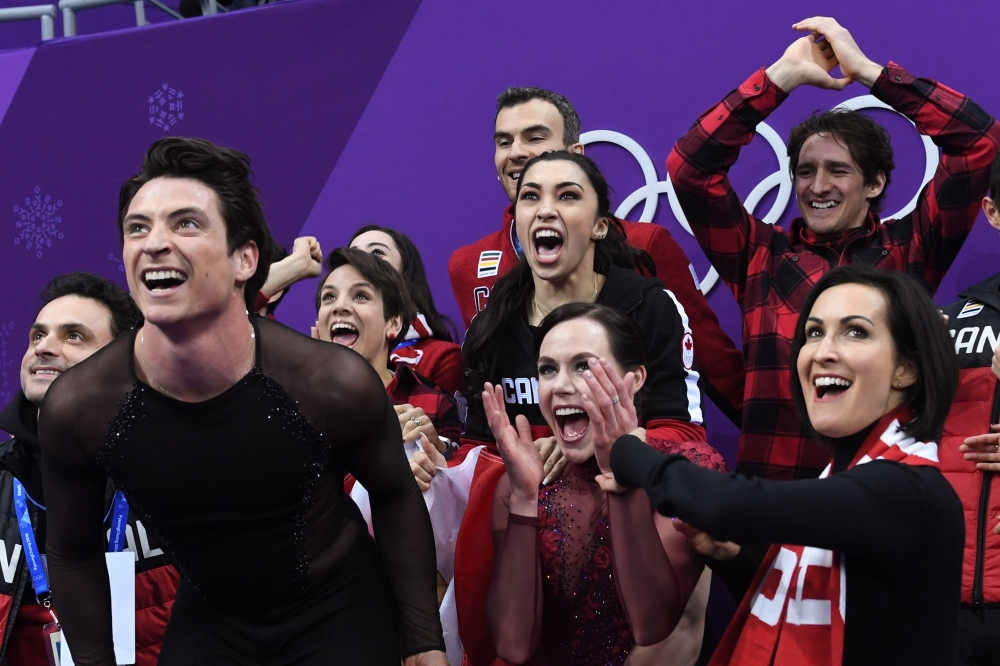 Canada's Scott Moir (L) and Canada's Tessa Virtue (C) react after competing in the figure skating team event ice dance free dance during the Pyeongchang 2018 Winter Olympic Games at the Gangneung Ice Arena in Gangneung on Monday. — AFP