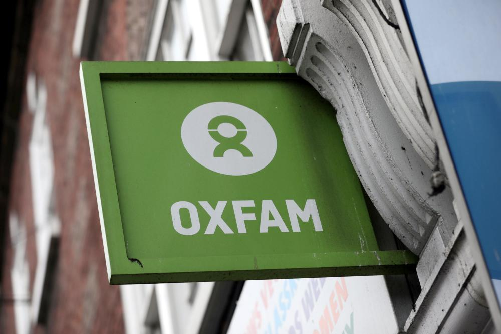 A sign is seen above a branch of Oxfam, in central London, Britain, on Tuesday. — Reuters