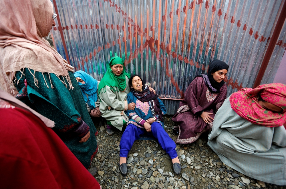 People console a woman who mourns the death of Mohammad Iqbal Sheikh, an Indian army officer, and his father, who according to local media were killed in Saturday's militant attack on Sunjwan Army camp in Jammu, in south Kashmir's Pulwama district, on Tuesday. — Reuters
