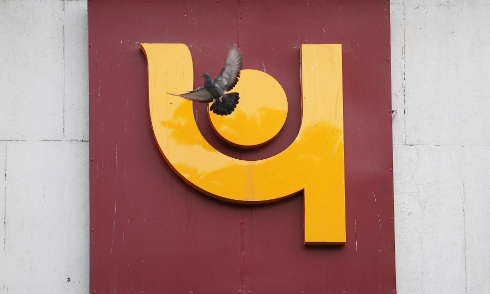 A pigeon flies past the logo of Punjab National Bank outside a branch of the bank in New Delhi, India, on Thursday. — Reuters