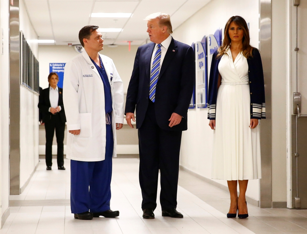 US President Donald Trump and first lady Melania Trump visit with Dr. Igor Nichiporenko, trauma surgeon at Broward Health North Hospital in the wake of the shooting at Marjory Stoneman Douglas High School in Pompano Beach, Florida, on Friday. — Reuters