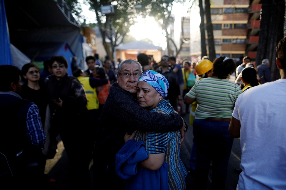 People react after an earthquake shook buildings in Mexico City, Mexico, on Friday. — Reuters