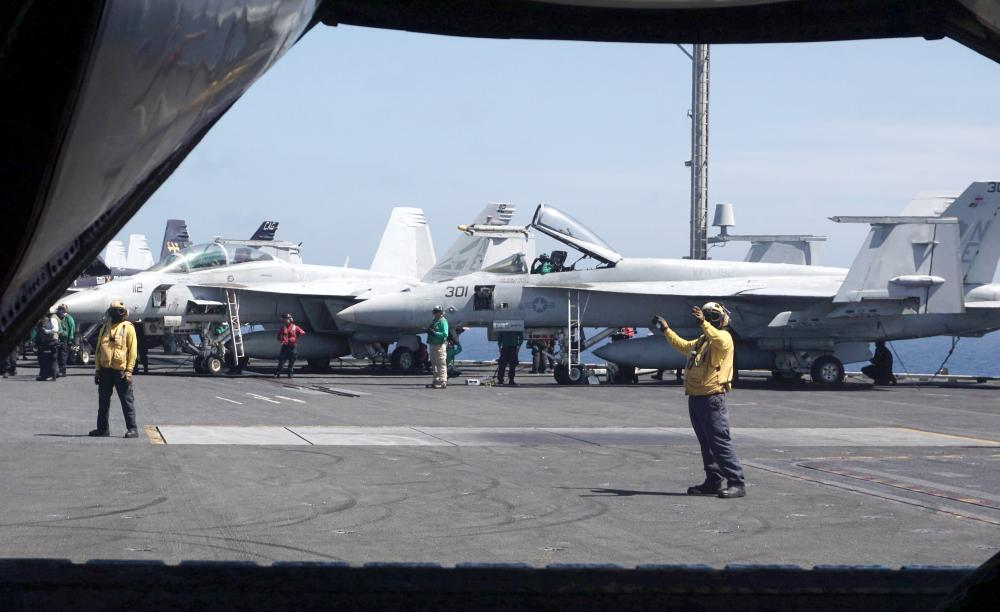 Sailors work next to F-18 Hornet fighter jets on the flight deck of the aircraft carrier USS Carl Vinson, as the carrier strike group goes on a routine deployment mission in the South China Sea, one hour away from Manila, in this Feb. 14, 2018 file photo. — AFP