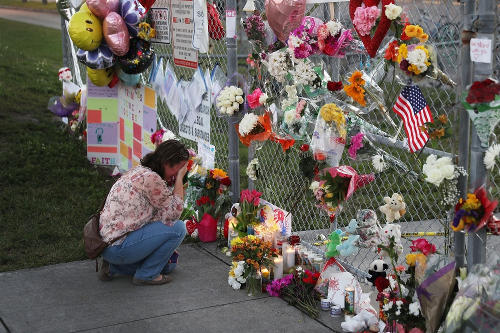 Melissa Goldsmith is over come with emotion as she visits a makeshift memorial setup in front of Marjory Stoneman Douglas High School on Sunday in Parkland, Florida. - AFP