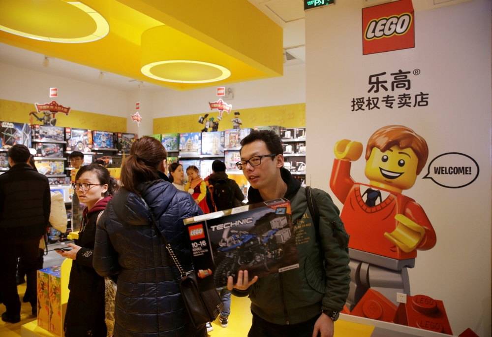 A customer carries a Lego box at a Lego store in Beijing, China. - Reuters