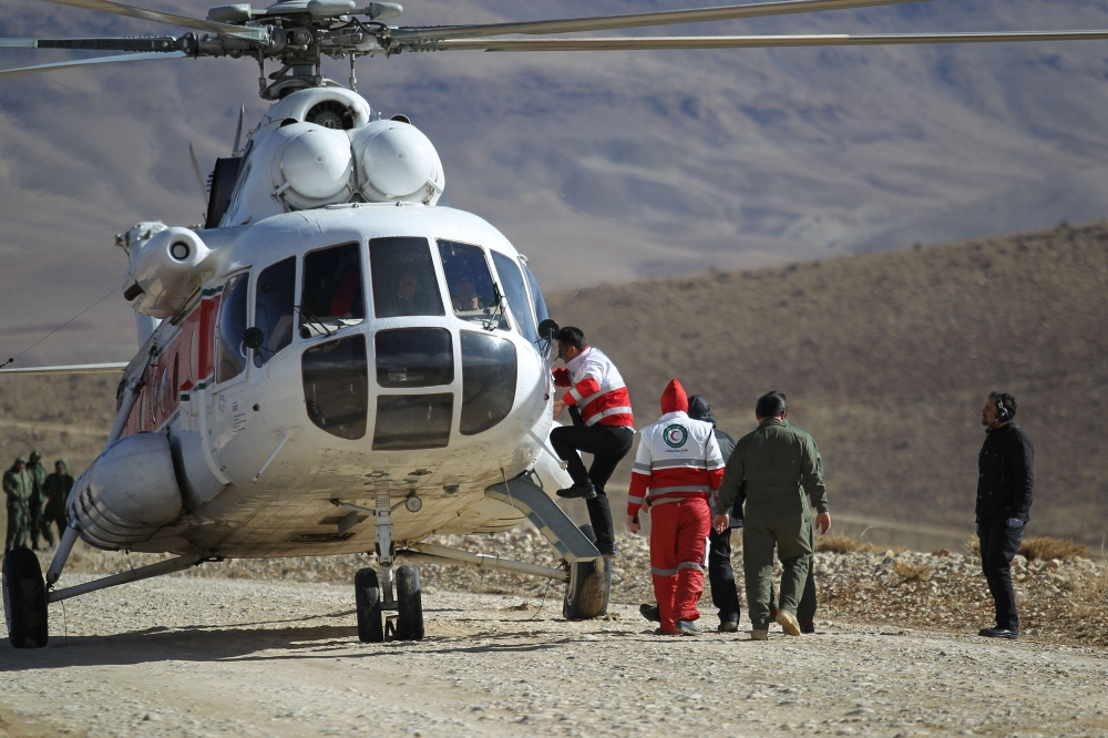 Members of emergency and rescue team search for the plane that crashed in a mountainous area of central Iran. — Reuters