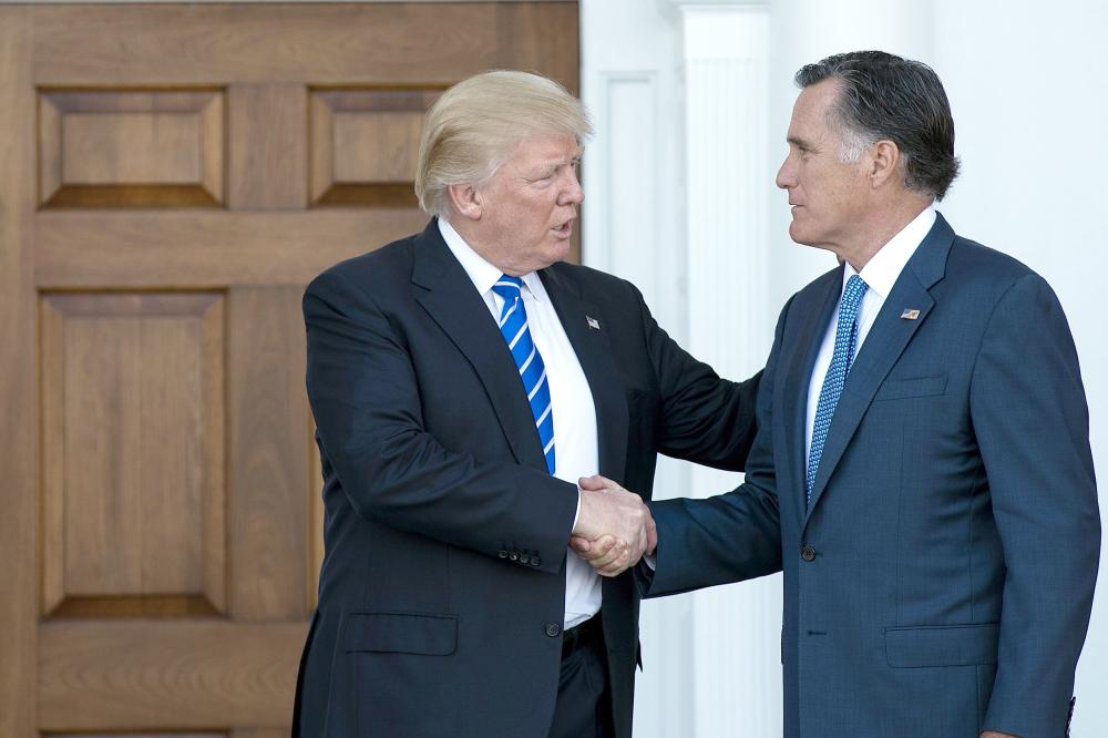 President Donald Trump shakes hands with Mitt Romney after their meeting at Trump International Golf Club in Bedminster Township, New Jersey, in this Nov. 19, 2016 file photo. — AFP