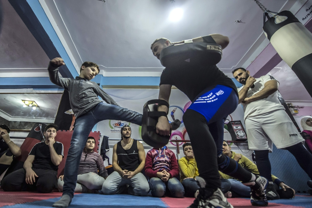 Syrian refugee Amir Al-Awad (R) watches as Adel Bazmawi (C) teaches martial arts to youth at the academy in Egypt's second city of Alexandria. — AFP