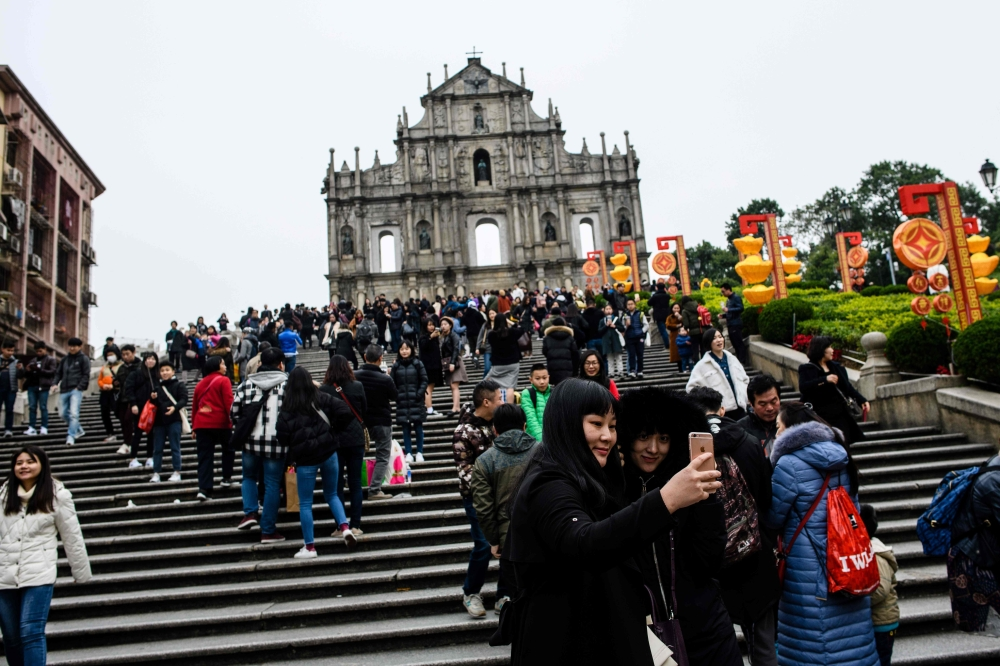 Tourists take a selfie in front of the southern stone facade of the ruins of St. Paul's Church, a 17th-century Portuguese complex in Santo Antonio in Macau. - AFP