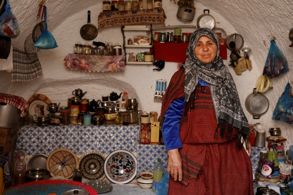 Mounjia, 60, poses for photograph in the kitchen of her troglodyte house.