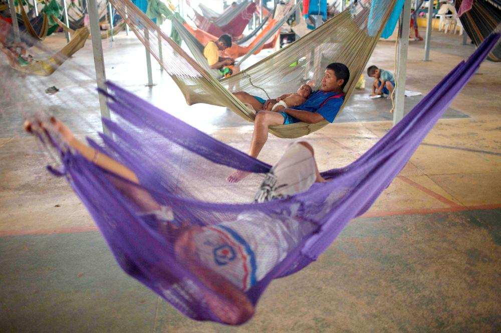 Venezuelan indigenous refugees rest on their hammocks, at a shelter in the city of Boa Vista, Roraima, Brazil, in this Feb. 24, 2018 file photo. — AFP
