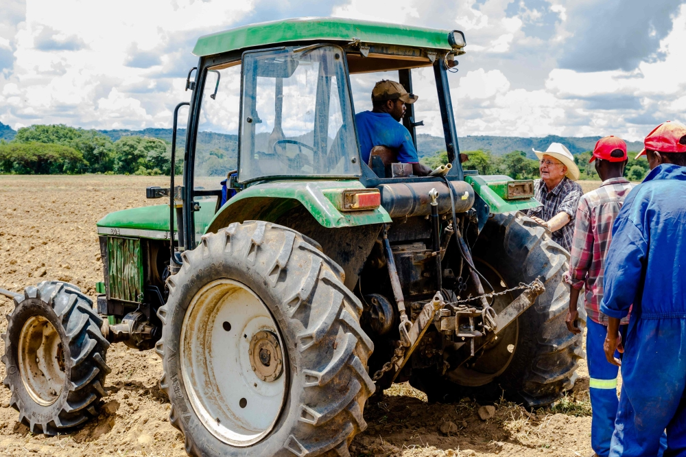 Zimbabwean commercial farmer Rob Smart (C) interacts with his workers as they prepare land for a potato crop at Lesbury Estates farm in Headlands east of the capital Harare. — AFP