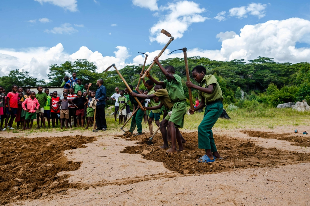 Pupils dig a longjump pit near the reopened school building at Lesbury Estates in Headlands east of the capital Harare, days after evicted white farmer Robert Smart was allowed to return to his land. — AFP