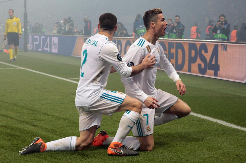 Real Madrid's Cristiano Ronaldo (R) celebrates with teammate Dani Carvajal after scoring the opening goal during their UEFA Champions League round of 16 second leg match against Paris Saint-Germain at the Parc des Princes Stadium in Paris Tuesday. — AFP