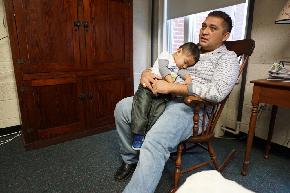 Business owner Oscar Canales holds his son, George, as he speaks during an interview at the Congregational United Church of Christ where he is living in sanctuary in Greensboro, North Carolina, in this Feb. 12, 2018 file photo. — AFP