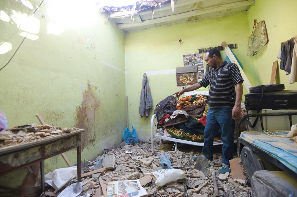 A picture taken Monday in Um Al-Hammam district in Riyadh shows a man inspecting damages to a home hit by falling shrapnel from Yemeni rebel missiles that were intercepted over the Saudi capital. Spokesman of Civil Defense in Riyadh Maj. Mohammed Al-Hammadi said that the Civil Defense teams in the city responded to the falling shrapnel from missiles after their interception on residential neighborhoods in different locations on Sunday. One of the shrapnel fell on a house in which an Egyptian expat was killed and two of his compatriots were injured, Saudi Press Agency quoted Al-Hammadi as saying. — AFP