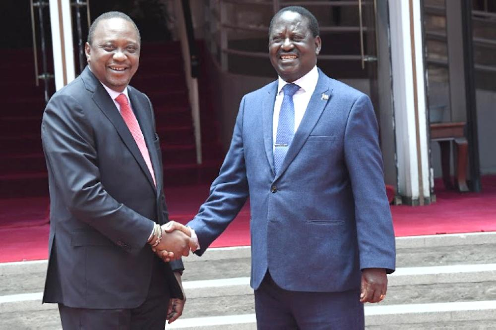 Kenya's President Uhuru Kenyatta, left, and National Super Alliance (NASA) coalition opposition leader Raila Odinga shake hands after addressing a press conference at Harambee house office in Nairobi in this March 9, 2018 file photo. — AFP