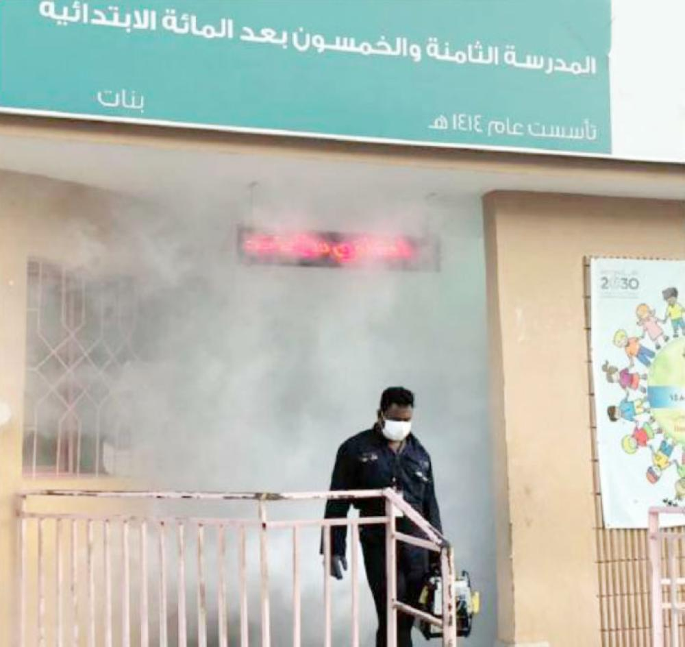 A worker comes out of a school building in Jeddah after sanitizing the premises. officials said as many as 77 medical teams are fighting the diseases and stop it from spreading to other areas. — Okaz photo