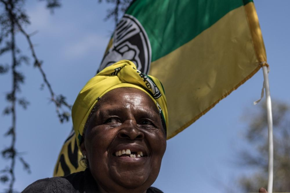 A woman dressed in African National Congress (ANC) regalia waits outside the Fourways Memorial Park in Johannesburg on Saturday, ahead of the burial of anti-apartheid icon Winnie Madikizela-Mandela. South Africans turned out in their thousands to bid final goodbyes to the anti-apartheid icon and Nelson Mandela's former wife who was laid to rest with full state honors. — AFP