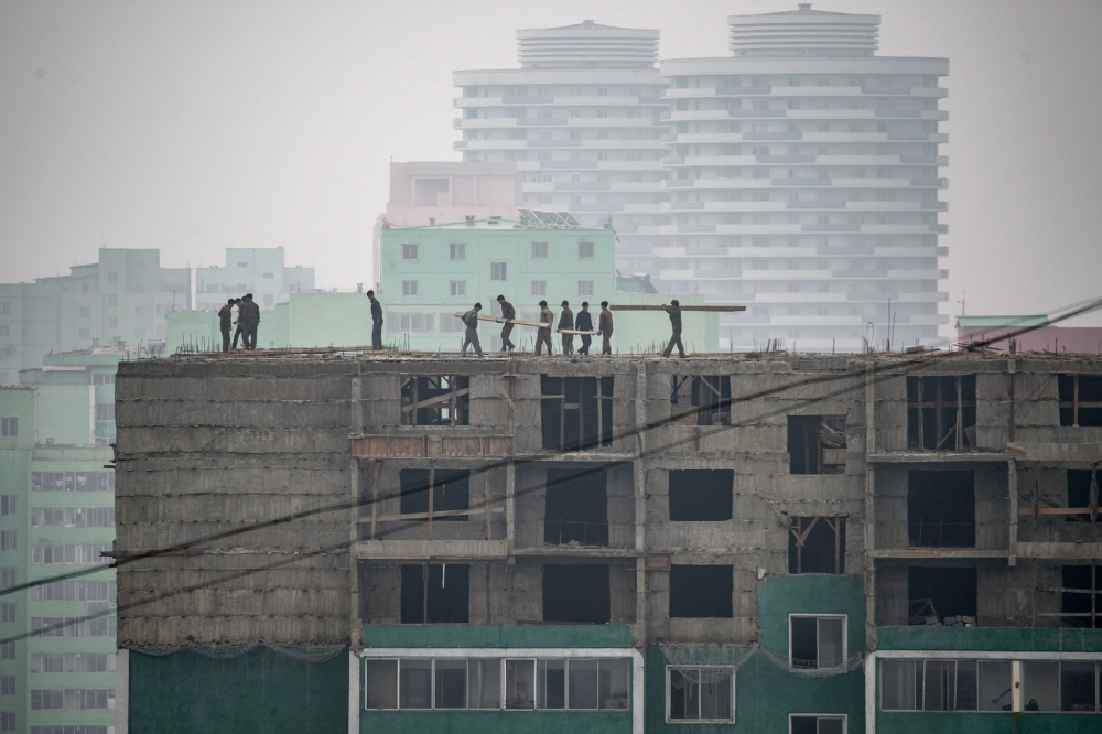 A construction site in Pyongyang in June. Sanctions limit the North's imports of petroleum, leaving the country without enough fuel to run all of its 280,000 cars, much less heat homes and meet other needs. — AFP