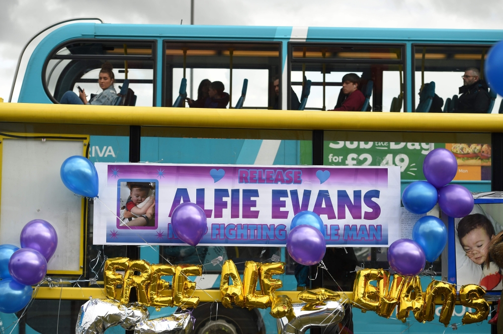 A bus passes balloons and posters left in support of British toddler Alfie Evans, on a bus stop opposite Alder Hey children's hospital in Liverpool, north-west England, in this April 26, 2018 file photo. — AFP
