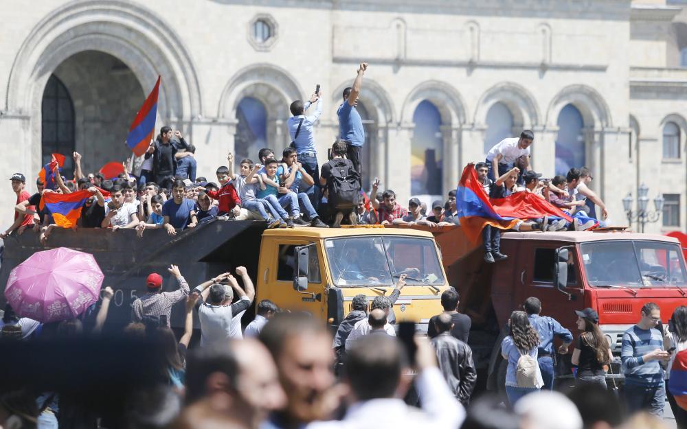 Armenian protesters ride on trucks as they block a street in Yerevan, Armenia, on Wednesday. — EPA