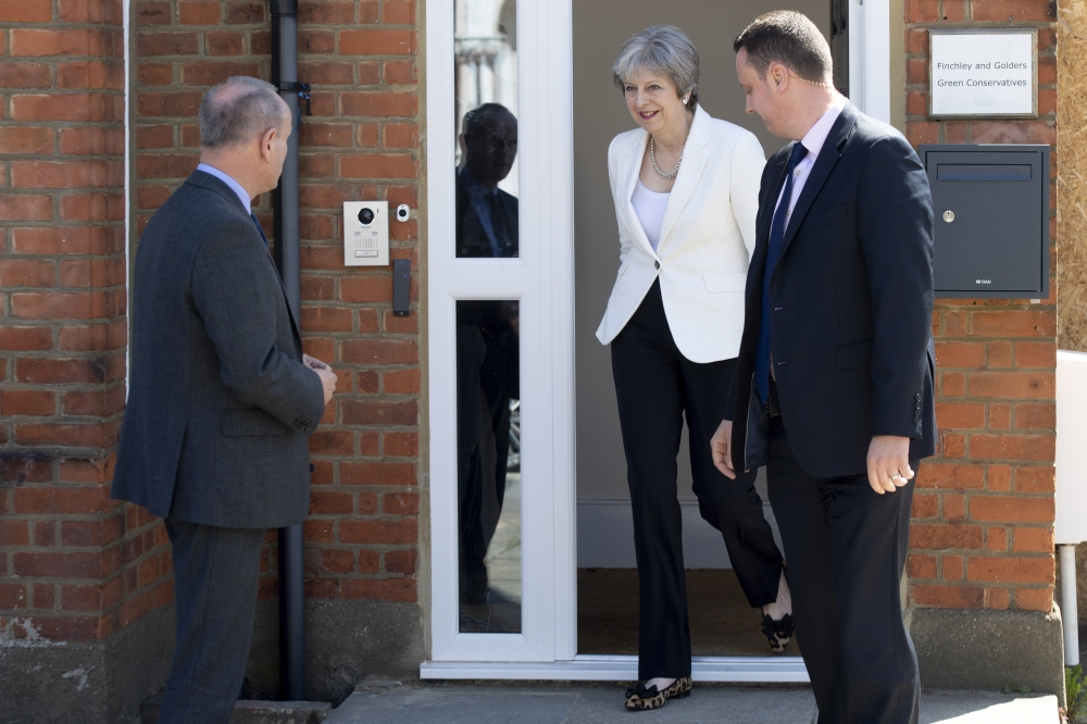 British Conservative Prime Minister Theresa May, center, leaves the Finchley and Golders Green Conservatives Association in north London, Britain, on Friday. — EPA