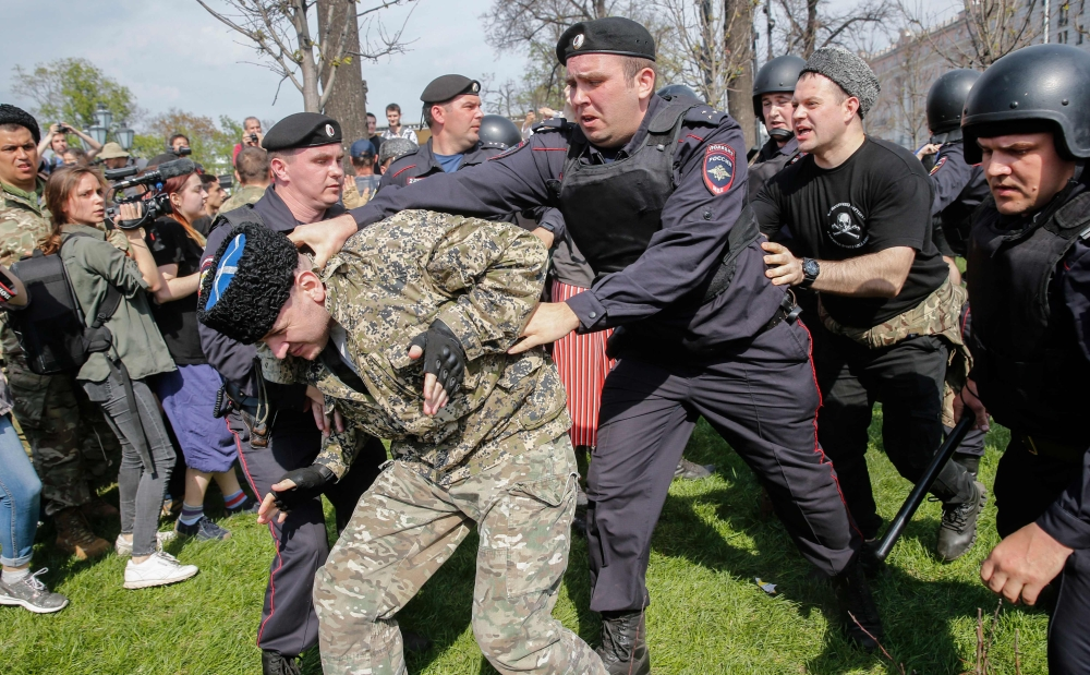 Russian police officers detain a Cossack during an unauthorized anti-Putin rally called by opposition leader Alexei Navalny in Moscow on Saturday. — AFP