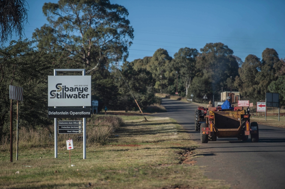 Workers drive past a sign of the Sibanye-Stillwater Driefontein gold mine near Carletonville, near Johannesburg, on Saturday. — AFP