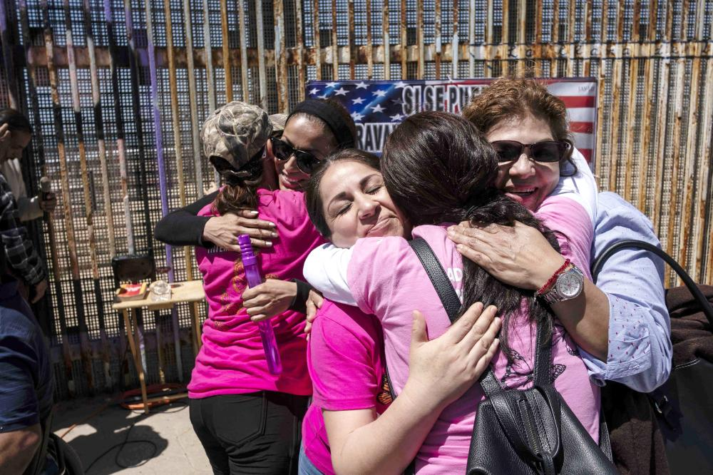 """""""Dreamers Moms International"""" celebrate Mother's Day and their fourth Anniversary near the US/Mexico border in Playas de Tijuana, Baja California State, Mexico, on Sunday. — AFP"""