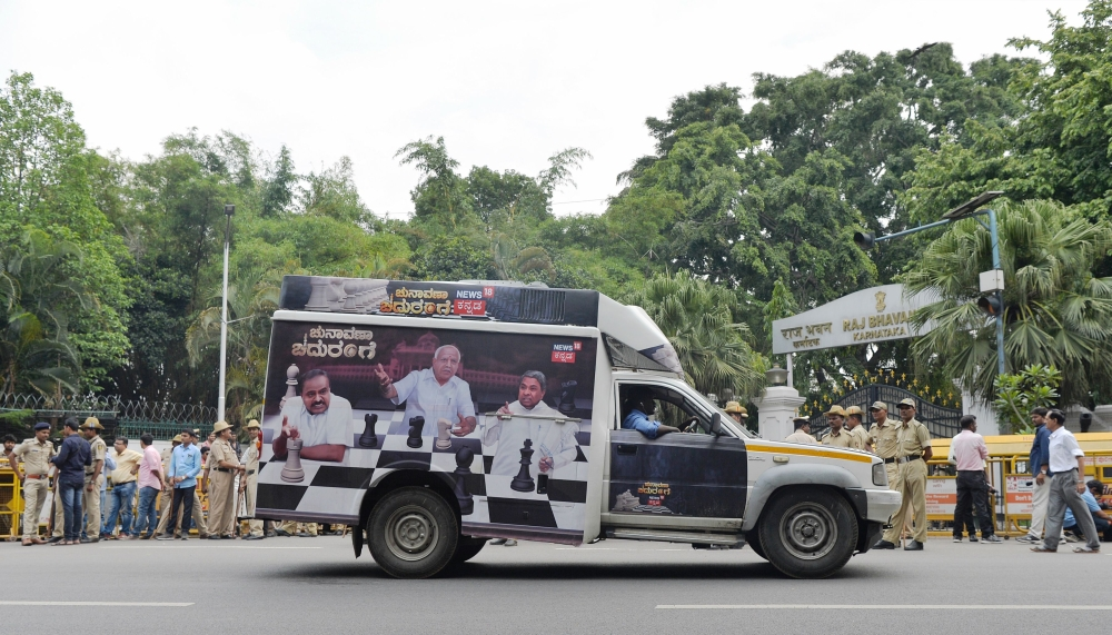 A vehicle depicting the current political scenario in the state passes by in front of Raj Bhavan, the residence of the state Governor Vajubhai Rudabhai Vala, in Bangalore on Wednesday. — AFP