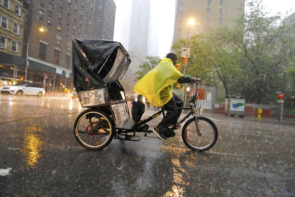 A pedicab driver peddles down Ninth Avenue at 57th Street during severe thunderstorm in New York City, New York, on Tuesday. — EPA