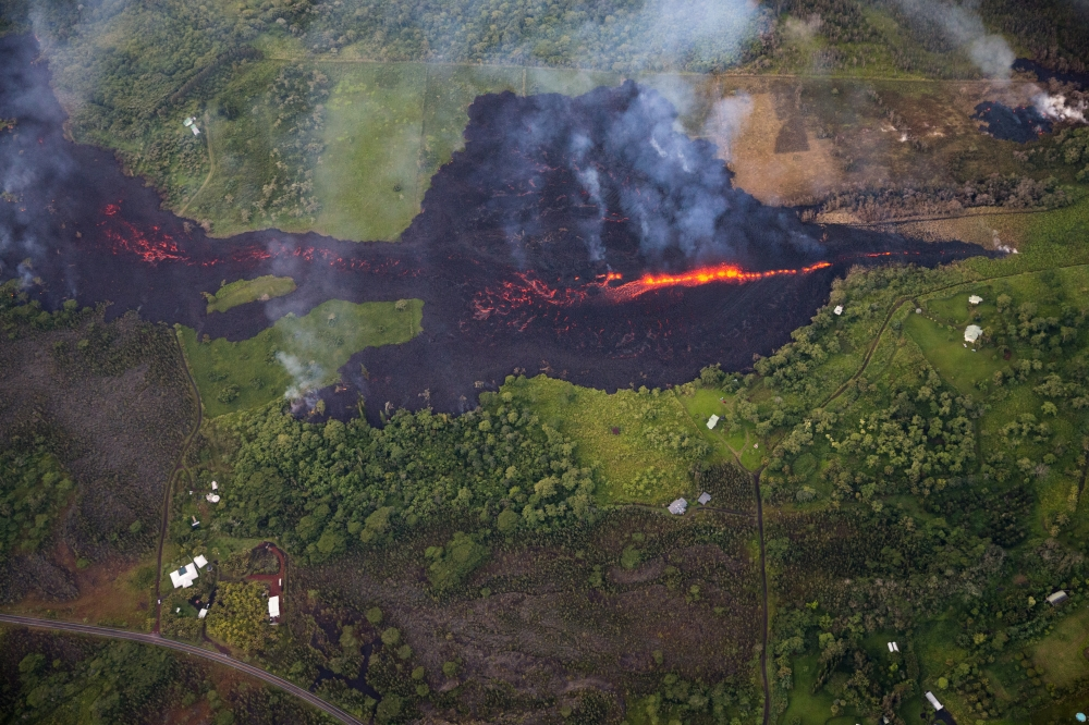 An aerial view shows eruptive activity continuing at fissure 17, as lava from that vent advanced roughly a mile, covering property, mainly pastureland, but is now encroaching upon two major thoroughfares, and a number of homes, in Pahoa, Hawaii, on Monday. — EPA