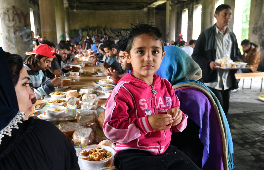 Migrants and their children are having lunch in an abandoned building in the north-western Bosnian town of Bihac. The building is being refitted with infrastructure to accept African-Asian migrants who make their stop in Bihac, where they rest before continuing