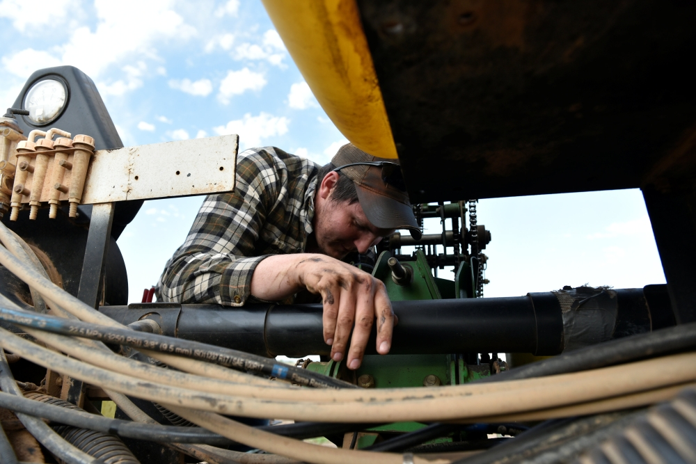 Farmhand Andrew Weaver works to replace a hydraulic hose on a planting implement in Wakita, Oklahoma, US. — Reuters