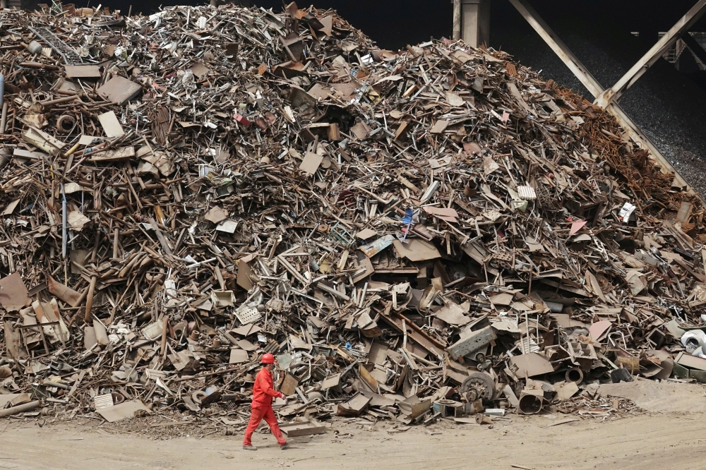 A worker walks past piles of scrap steel at a plant of Dongbei Special Steel Group Co Ltd in Dalian, Liaoning province, China. — Reuters