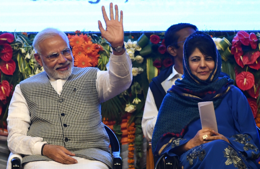 Indian Prime Minister Narinder Modi waves next to Jammu and Kashmir Chief Minister Mehbooba Mufty during the inauguration if the 330mw Kishenganga Hydel Project in Srinagar on Saturday. — AFP
