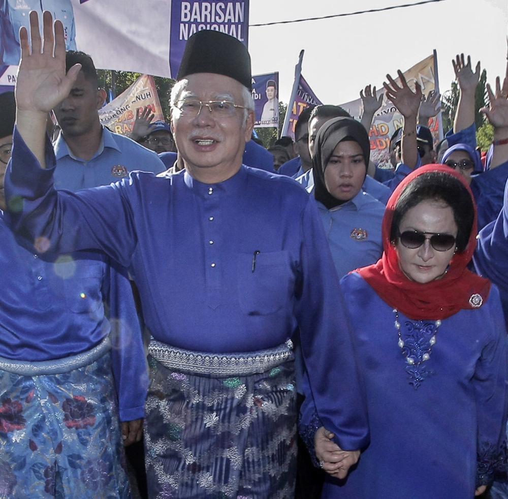 Then Malaysian Prime Minister and National Front coalition (Barisan Nasional) President Najib Razak, left, holds hands with his wife Rosmah Mansor, right, as they walk together to submit Razak's nomination for the 14th general elections, in Pahang, some 300 km from Kuala Lumpur, Malaysia, in this April 28, 2018 file photo. — EPA