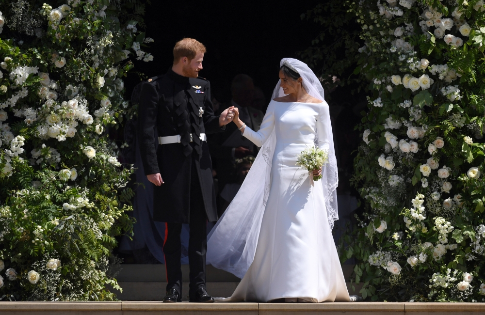 Britain's Prince Harry, Duke of Sussex and Meghan, Duchess of Sussex exit St George's Chapel in Windsor Castle after their royal wedding ceremony, in Windsor on Saturday. - EPA
