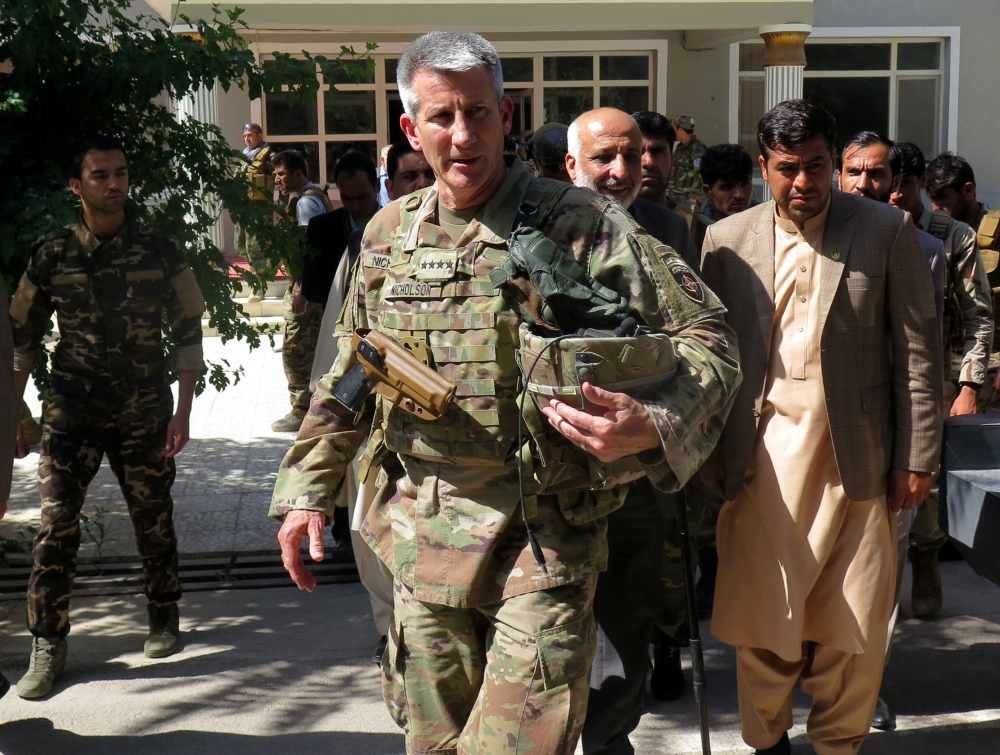 US Army General John Nicholson, commander of Resolute Support forces and US forces in Afghanistan, walks with Afghan officials during an official visit in Farah province, Afghanistan, on Saturday. — Reuters