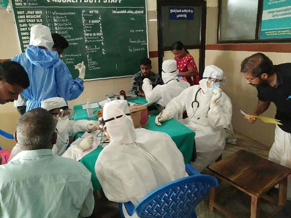 Medical personnel wearing protective suits check patients at the Medical College hospital in Kozhikode, Kerala, on Monday. — AFP